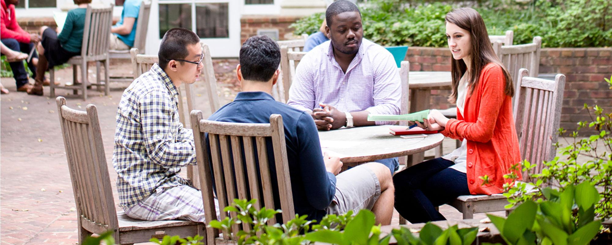 Four students meeting at table on Newcomb Hall outdoor patio